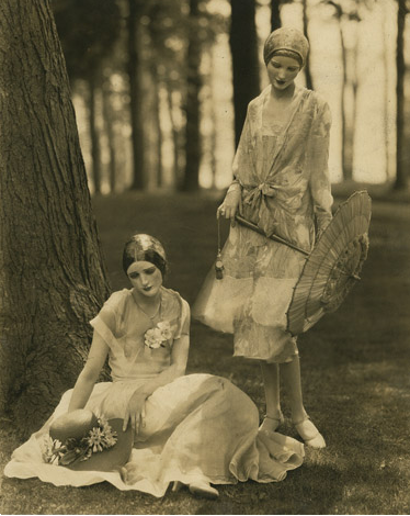 Model Marion Morehouse in a bouffant dress and actress Helen Lyons in a long sleeve dress by Kargère; masks by the illustrator W.T. Benda, 1926