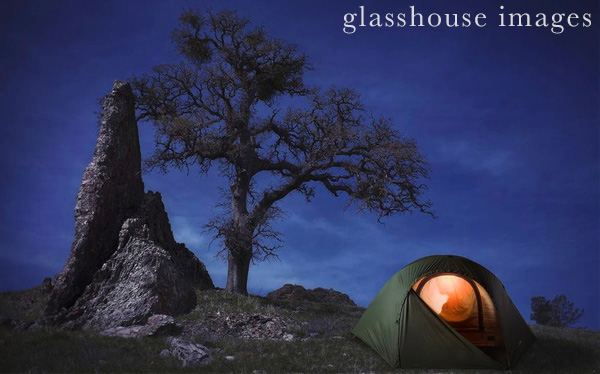 Person in Illuminated Tent on Hilltop Near Tree and Rock Formation at Night